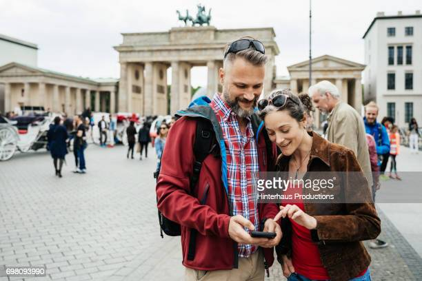 Mature Couple Looking Over Photos They Have Taken At Brandenburg Gate in Berlin