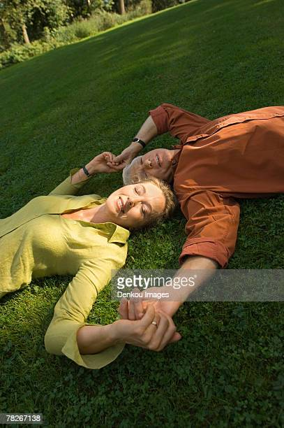 a mature couple lying down on the grass. - down blouse stockfoto's en -beelden