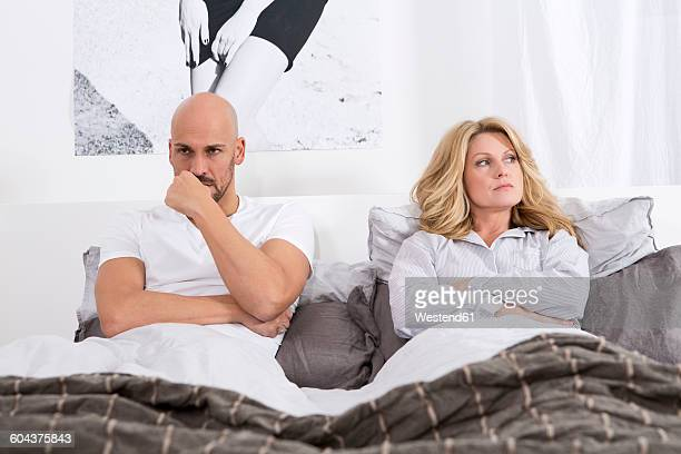 Mature couple lying in bed, having relationship problems