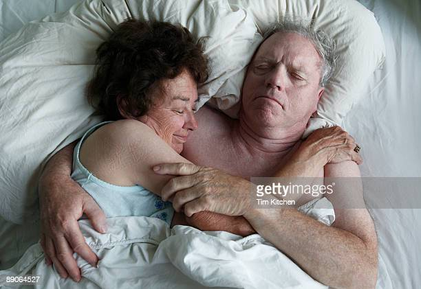 Mature couple lying in bed, man embracing woman