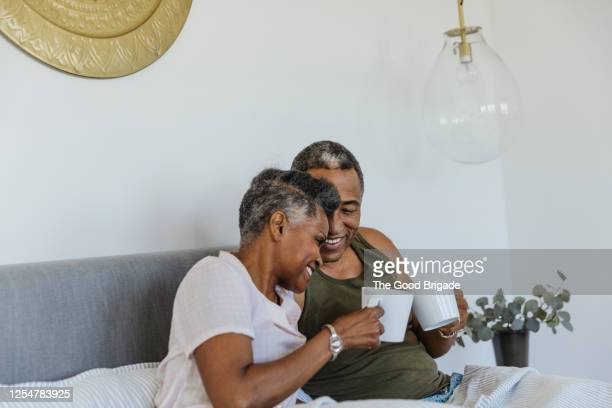 mature couple lying in bed - disruptaging stock-fotos und bilder