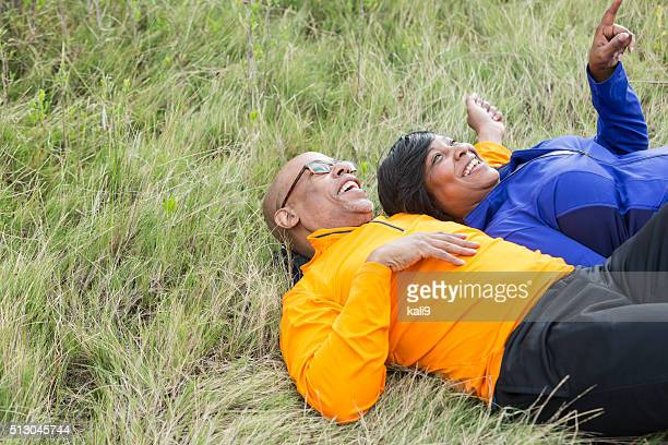 Mature couple lying on backs in park looking at sky