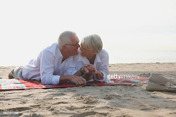 Mature couple lying on beach blanket