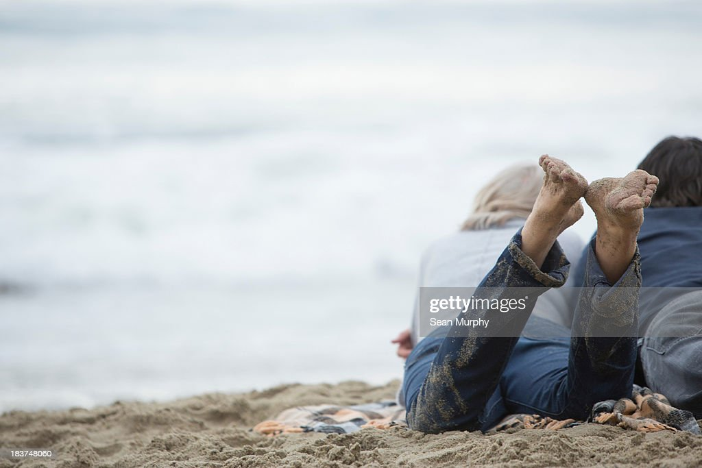 Mature couple lying on beach looking at sea : Stock Photo