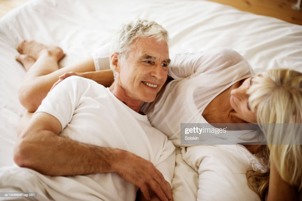 Mature couple lying on bed : Stock Photo