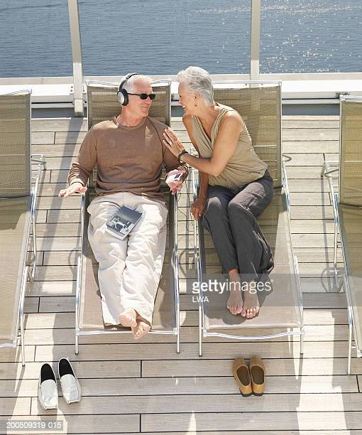 Mature couple lying on deck on ship, smiling