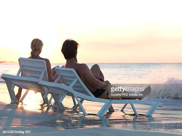 Mature couple lying on sun lounger, rear view