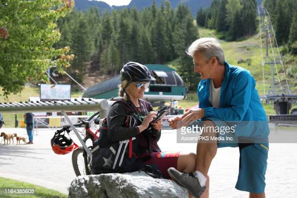 mature couple make an online purchase below the bike park - early retirement stock pictures, royalty-free photos & images