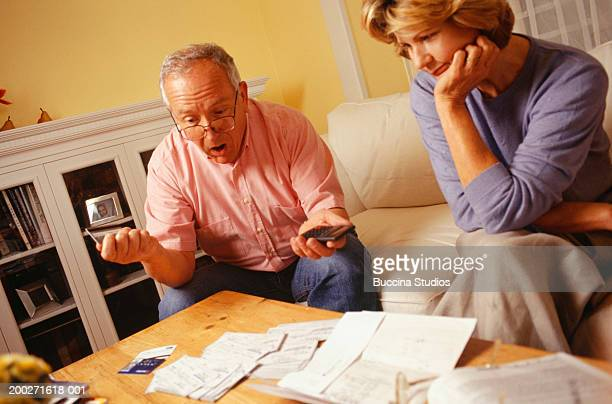 Mature couple managing finances in living room