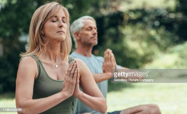 reifes paar meditieren zusammen während yoga-praxis draußen - husband stock-fotos und bilder