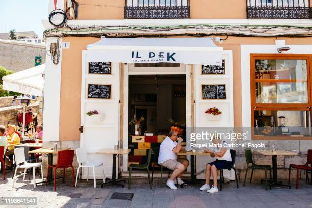 Mature couple of tourists sit at an italian bistrot restaurant terrace in La Marina neighborhood