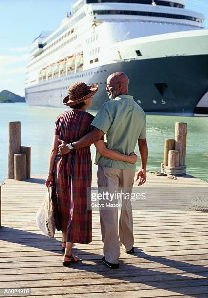 mature couple on a pier near a cruise ship - cruise ship stock pictures, royalty-free photos & images