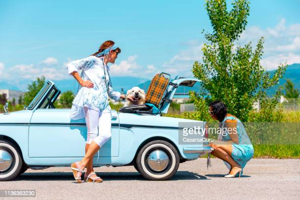 mature couple on a road trip fixing a broken vintage car - pastore maremmano foto e immagini stock