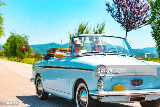 mature couple on a road trip with a vintage car - italy stock pictures, royalty-free photos & images