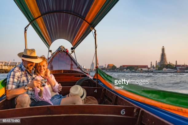 mature couple on a romantic sunset boat cruise on the river in bangkok thailand - bangkok stock photos and pictures