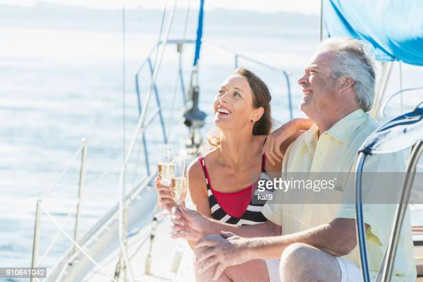Mature couple on a sailboat drinking champagne