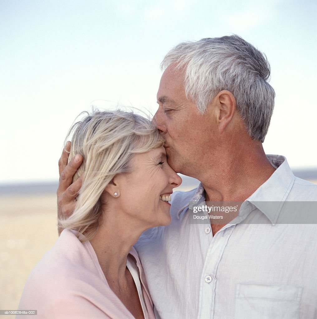 Mature couple on beach, man kissing woman on forehead : Stock Photo