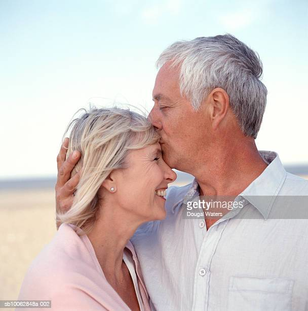 Mature couple on beach, man kissing woman on forehead