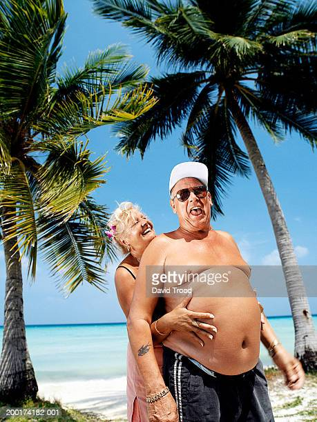 mature couple on beach smiling, woman embracing man from behind - dicke frauen am strand stock-fotos und bilder