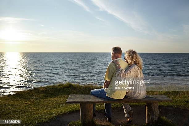 Mature couple on bench watching sunset over ocean