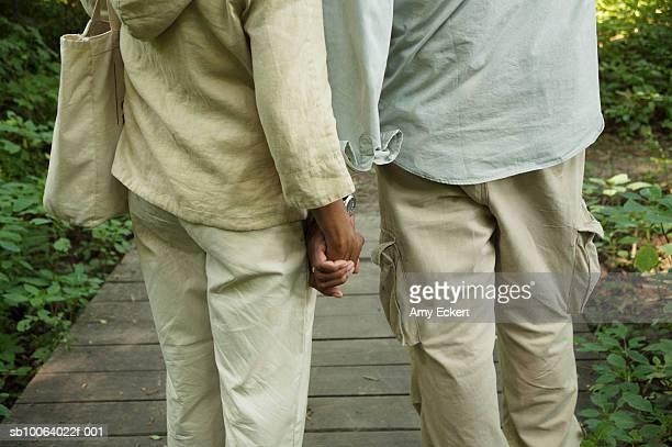 mature couple on boardwalk, holding hands, mid section - 55 59 jahre stock-fotos und bilder