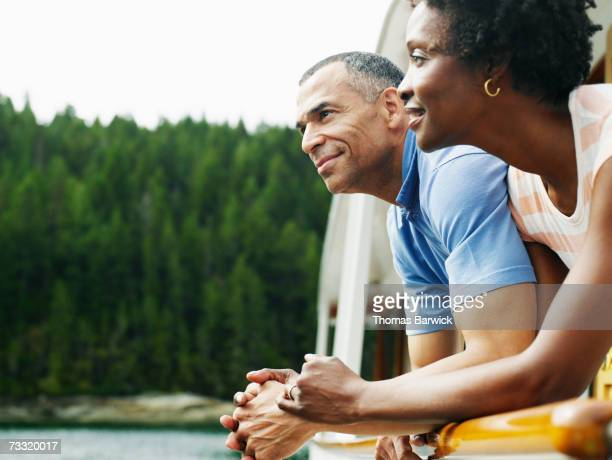 mature couple on deck of yacht looking at view, smiling - african american couple stock pictures, royalty-free photos & images