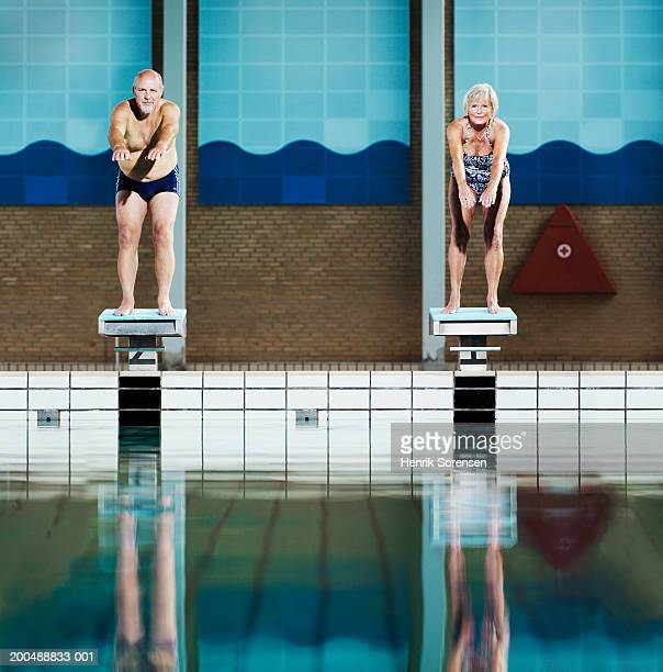 Mature couple on diving boards in swimming pool, portrait