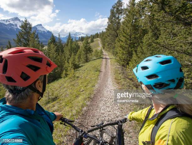 mature couple on electric mountain bikes relax on trail - early retirement stock pictures, royalty-free photos & images