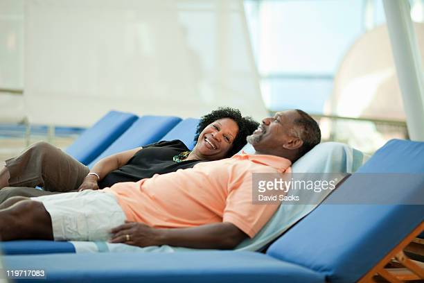 mature couple on lounge chair on cruise ship - cruise vacation stock pictures, royalty-free photos & images