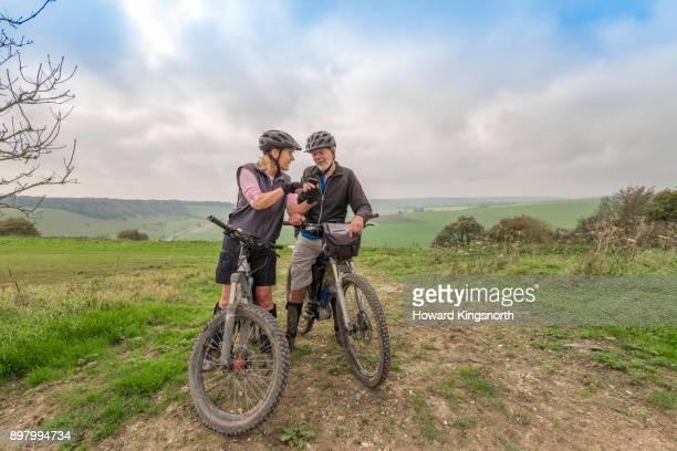mature couple on mountain bikes checking directions - hügelkette stock-fotos und bilder