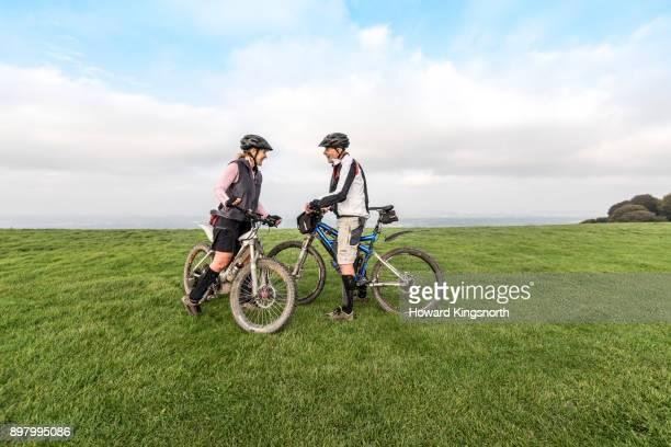 mature couple on mountain bikes in rural setting - hügelkette stock-fotos und bilder