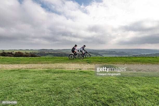 mature couple on mountain bikes in wide landscape - hügelkette stock-fotos und bilder
