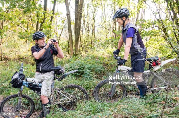 mature couple on mountain bikes photographing each other