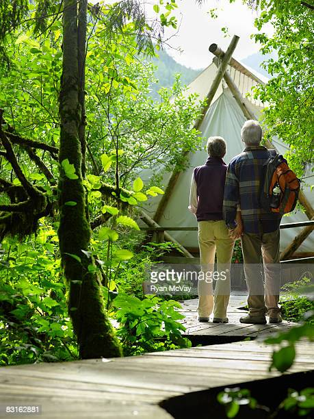 Mature couple on pathway outside tent.