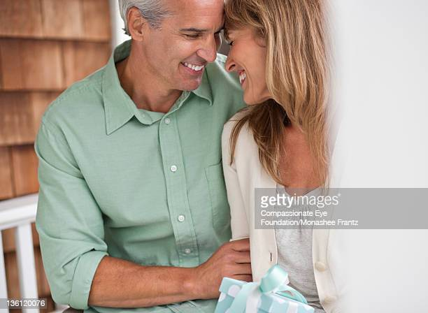 """mature couple on porch swing, smiling - """"compassionate eye"""" stock pictures, royalty-free photos & images"""