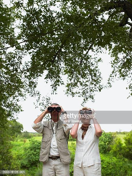 Mature couple on safari, standing under tree using binoculars, smiling