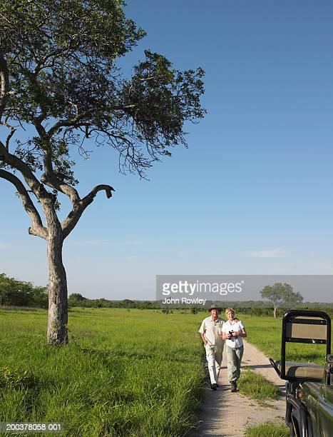 Mature couple marche sur safari en 4 x 4 sur la piste, souriant