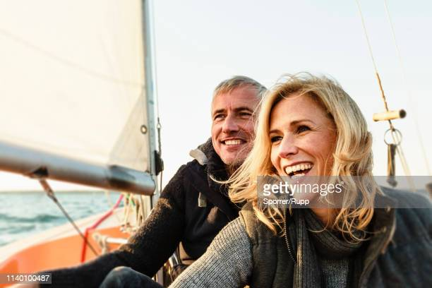 mature couple on sailing boat, smiling - sailor stock pictures, royalty-free photos & images