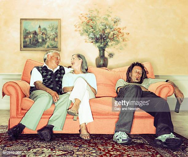 mature couple on sofa beside man holding television remote - generation gap stock pictures, royalty-free photos & images