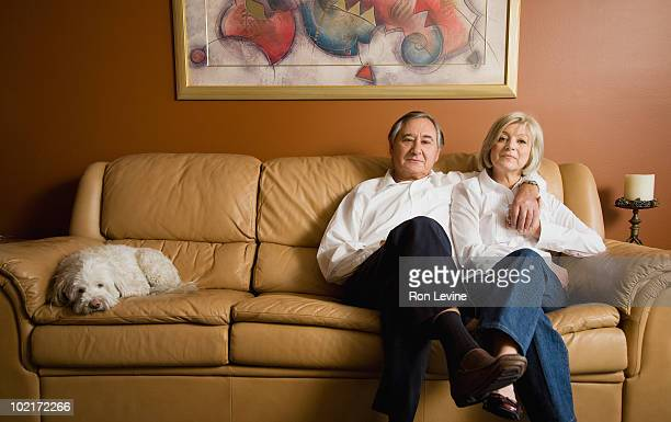 Mature couple on sofa with their pet dog