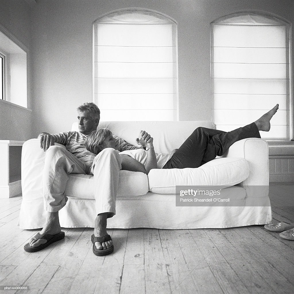 Mature couple on sofa, woman leaning head on man's stomach, b&w : Stockfoto