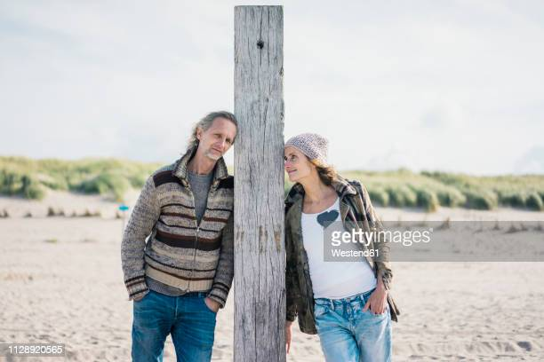 Mature couple on the beach, leaning on wood pole