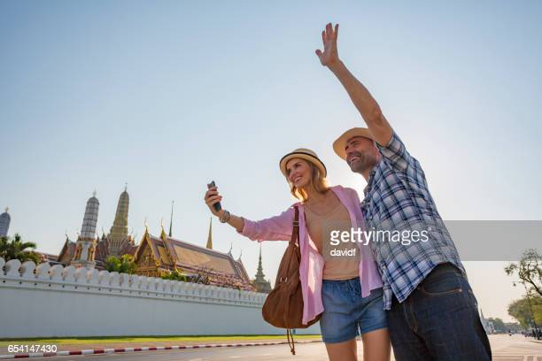 Mature Couple on Vacation in Thailand Using a Phone App To Catch a Taxi
