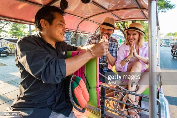 Älteres Paar im Urlaub zahlen respektvoll Tuktuk Transporttreiber in Thailand