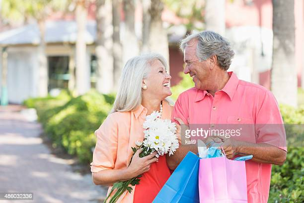 Mature couple outdoors carrying shopping bags