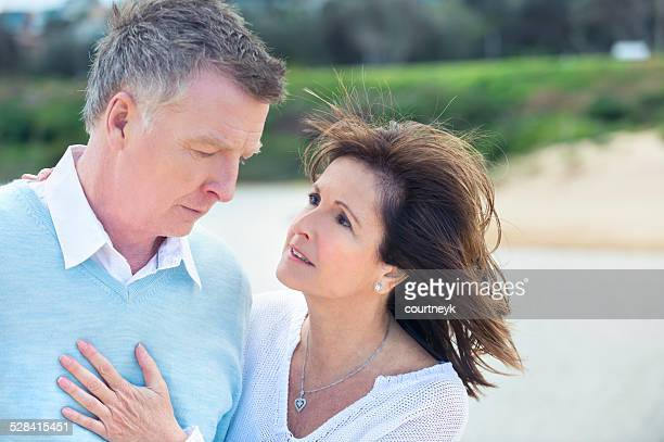 Mature couple outdoors grieving and upset
