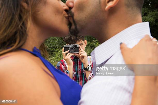 Mature couple outdoors, kissing, son taking photograph of them, using camera