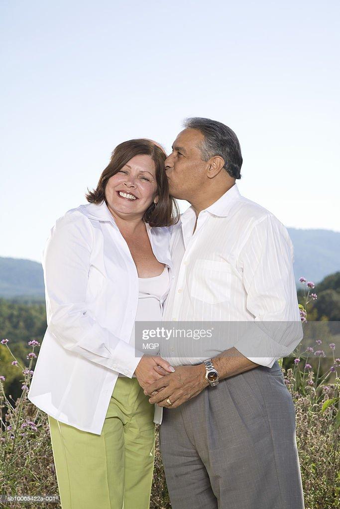 Mature couple outdoors, man kissing woman : Foto stock