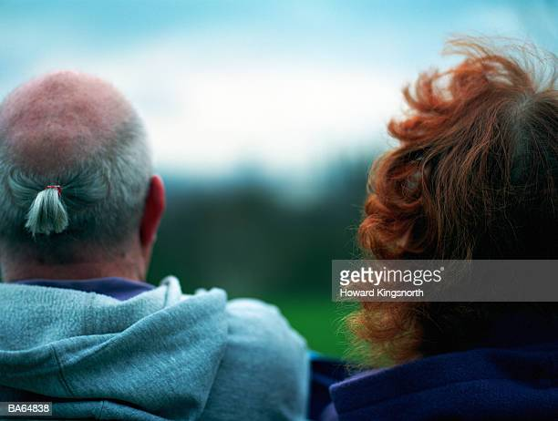 Mature couple outdoors, rear view, close-up