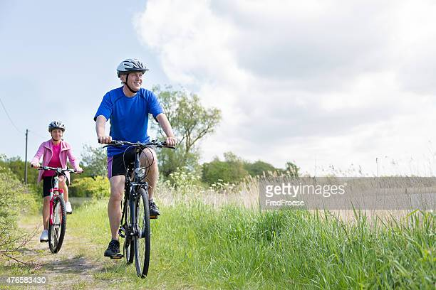 Mature couple outdoors riding bikes in the nature
